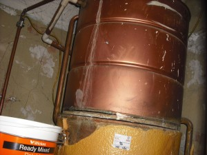 Hot water tank with asbestos millboard separating the two tanks.